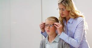 Θηλυκό optometrist που ορίζει τα θεάματα στο νέο ασθενή απόθεμα βίντεο
