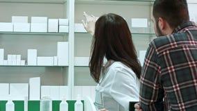 Θηλυκό parmacist και νέος αρσενικός πελάτης στο φαρμακείο απόθεμα βίντεο