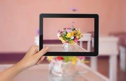 Θηλυκό PC ταμπλετών εκμετάλλευσης χεριών με τις εικόνες λουλουδιών στην οθόνη Στοκ Εικόνες