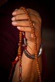 Θιβετιανό χέρι που κρατά τις βουδιστικές χάντρες προσευχής, ναός Boudhanath, Κ Στοκ Φωτογραφία