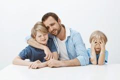 Θλίψη πατέρων με τους γιους καθμένος στον πίνακα, αγκαλιάζοντας το αγόρι και φωνάζοντας, που ανατρέπεται και δυστυχισμένος ενώ νε Στοκ φωτογραφία με δικαίωμα ελεύθερης χρήσης