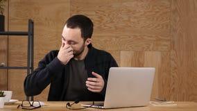 Θλιβερός για αυτόν Γενειοφόρος νέος εργαζόμενος του τηλεφωνικού κέντρου απόθεμα βίντεο