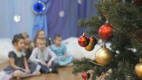Θολωμένα παιδιά που κάθονται κοντά στο χριστουγεννιάτικο δέντρο στο εσωτερικό φιλμ μικρού μήκους