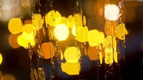 Θολωμένα περίληψη φω'τα πόλεων νύχτας και bokeh πίσω από το υγρό γυαλί με τις σταγόνες βροχής απόθεμα βίντεο
