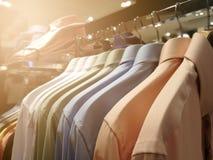 Θολωμένα πουκάμισα των ατόμων στα διαφορετικά χρώματα στις κρεμάστρες σε ένα λιανικό γ Στοκ Φωτογραφίες