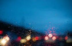 Θολωμένα φω'τα αυτοκινήτων από μέσα από ένα αυτοκίνητο με τις πτώσεις στο παράθυρο στοκ εικόνες με δικαίωμα ελεύθερης χρήσης