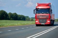 θολωμένη γωνία όψη truck μεταφορών κινήσεων επίδρασης ευρέως Εμπορικό όχημα με το κόκκινο αμάξι στην εθνική οδό Trucker επαγγέλμα Στοκ φωτογραφία με δικαίωμα ελεύθερης χρήσης
