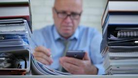 Θολωμένη εικόνα με έναν επιχειρηματία χρησιμοποιώντας το κινητό τηλέφωνο και γράφοντας τα έγγραφα απόθεμα βίντεο
