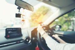 Θολωμένη εικόνα των γυναικών που οδηγούν ένα αυτοκίνητο στο δρόμο, θηλυκός οδηγός Στοκ Φωτογραφία