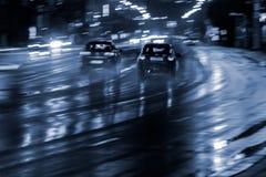 Θολωμένη οδήγηση αυτοκινήτων στον υγρό δρόμο μετά από τη βροχή Κυκλοφορία πόλεων νύχτας Στοκ Εικόνες