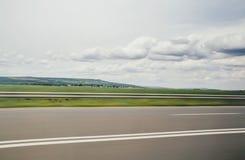 Θολωμένη φωτογραφία θαμπάδων κινήσεων του σιδηροδρόμου autobahn Τεράστια μεγάλα άσπρα άσπρα σύννεφα ανωτέρω Στοκ Φωτογραφία