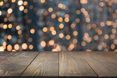 Θολωμένη χρυσή γιρλάντα και ξύλινο tabletop ως πρώτο πλάνο Εικόνα για την επίδειξη ή montage τα προϊόντα Χριστουγέννων σας Στοκ Εικόνες