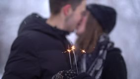 Θολωμένοι αριθμοί του φιλήματος νεαρών άνδρων και γυναικών στο υπόβαθρο του καψίματος sparkler στο χιονισμένο πάρκο Χειμώνας φιλμ μικρού μήκους