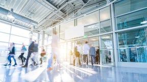 Θολωμένοι επιχειρηματίες σε μια αίθουσα εμπορικών εκθέσεων Στοκ Εικόνες
