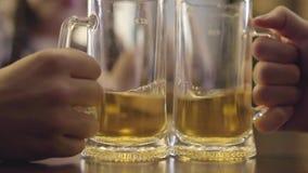 Θολωμένος αριθμός της γυναίκας με τις πλεξίδες που κάθονται στο μετρητή φραγμών με το ποτήρι της μπύρας Κουδούνισμα χεριών ατόμων φιλμ μικρού μήκους