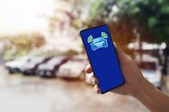 Θολωμένος ο υπόβαθρο χώρος στάθμευσης, smartphone εκμετάλλευσης άποψης ανοίγει την επικοινωνία με το όχημα για τη θέση και την ασ στοκ εικόνες