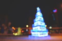 Θολωμένο εορταστικό υπόβαθρο που γίνεται με το χριστουγεννιάτικο δέντρο και τα φω'τα Νέο σκηνικό έτους στοκ εικόνα