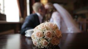 Θολωμένο ζεύγος των newlyweds που φιλά καθμένος στον καφέ μια ανθοδέσμη της νύφης στο πρώτο πλάνο φιλμ μικρού μήκους