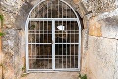Θολωτή μετάβαση ή σήραγγα πετρών με την πύλη σιδήρου Στοκ Φωτογραφία