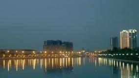 Θολωμένη άποψη της πόλης σε μια ακτή Προκυμαία πόλεων στη νύχτα με τα φω'τα των κτηρίων και των λαμπτήρων οδών απόθεμα βίντεο
