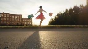 Θολωμένη γυναίκα Shopaholic στο όμορφο φόρεμα που κρατά πολλές τσάντες αγορών περπατώντας στην οδό μέσω του ήλιου κατά τη διάρκει απόθεμα βίντεο