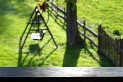 Θολωμένος κήπος άνοιξης/καλοκαιριού με το δέντρο και seesaw/την ταλάντευση Στοκ Φωτογραφίες