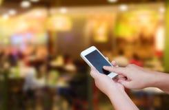 Θολωμένο έξυπνο τηλέφωνο οθόνης λαβής και αφής χεριών εικόνας στην περίληψη Στοκ Φωτογραφίες