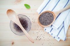 Θρεπτικοί σπόροι chia στο κύπελλο γυαλιού με το ξύλινο κουτάλι για τη διατροφή φ στοκ φωτογραφίες