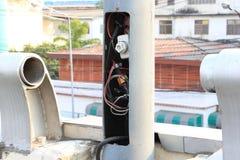 Θρυαλλίδα και ηλεκτρικά καλώδια μέσα στον πόλο λαμπτήρων Στοκ Εικόνες
