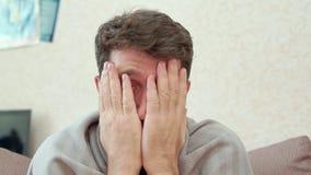 Θρύψαλα ατόμων Έχει ένα κρύο, πονοκέφαλος, πυρετός, ψύχρες Κάθισμα στον καναπέ απόθεμα βίντεο