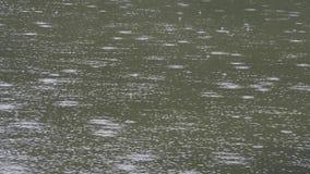 Θυελλώδης ημέρα με τις πτώσεις βροχής σε μια επιφάνεια λιμνών βουνών απόθεμα βίντεο