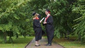 Θυελλώδης καιρός, ζευγάρι των πτυχιούχων που στέκονται στο πάρκο με τα διπλώματα, αέρας της αλλαγής φιλμ μικρού μήκους