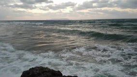 Θυελλώδης chopy θάλασσα με το ράντισμα των κυμάτων στην παραλία Tsalos ηλιο απόθεμα βίντεο
