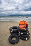 Θυελλώδες βράδυ στην παραλία με τα δραματικά σύννεφα και τα κύματα Με τα σακάκια ζωής και κολυμπήστε τα δαχτυλίδια στο πρώτο πλάν Στοκ εικόνα με δικαίωμα ελεύθερης χρήσης