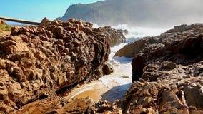 Θυελλώδες θαλάσσιο νερό που ορμά μέσα - μεταξύ των βράχων στην ακτή απόθεμα βίντεο