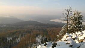 Θυελλώδης άποψη χειμερινού πρωινού στην ανατολή με την πορτοκαλιά ανατολή. Χαραυγή στους βράχους φιλμ μικρού μήκους