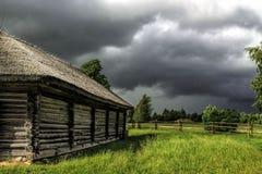 Θυελλώδης ουρανός και ξύλινο του χωριού σπίτι Στοκ Εικόνες