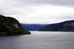 Θυελλώδης ουρανός πέρα από τα χιονώδεις βουνά και τον ποταμό στοκ φωτογραφία