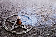 Θυμίαμα καψίματος στο κέντρο του γκρίζου μετάλλου pentagram στην πλάκα backg Στοκ Εικόνα