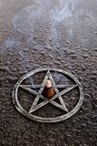 Θυμίαμα καψίματος στο κέντρο του γκρίζου μετάλλου pentagram στην πλάκα backg Στοκ Φωτογραφία