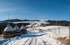 Θυμωνιές χόρτου στο χειμερινό χωριό Στοκ Φωτογραφίες