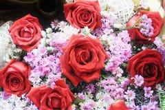 Θόλωσε μια ανθοδέσμη του κόκκινου άνθους λουλουδιών τριαντάφυλλων με τη μικρή γλυκιά ρόδινη άσπρη χλωρίδα στοκ εικόνες με δικαίωμα ελεύθερης χρήσης