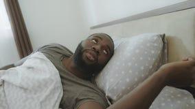 Θόρυβος ακούσματος μαύρων το πρωί Ενοχλημένο αρσενικό πρόσωπο που ξυπνά στο κρεβάτι απόθεμα βίντεο