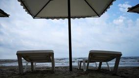 Θύελλα στην παραλία Μεγάλα γκρίζα κύματα και δροσερός καιρός Κενά κρεβάτια ήλιων ως έννοια της ταραχής φύσης απόθεμα βίντεο