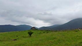 θλιβερός ουρανός επάνω από τα βουνά Ένα σπίτι είναι στα βουνά Στοκ Φωτογραφίες