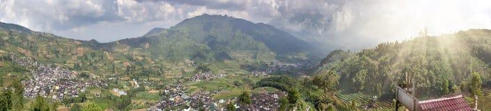 Ιάβα, Ινδονησία Μια άποψη από το δρόμο βουνών στους λόφους με τους πράσινους τομείς και το χωριό στην κοιλάδα Στοκ εικόνες με δικαίωμα ελεύθερης χρήσης