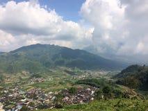 Ιάβα, Ινδονησία Μια άποψη από το δρόμο βουνών στους λόφους με τους πράσινους τομείς και το χωριό στην κοιλάδα Στοκ Φωτογραφία