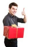 διακοπές Άτομο που δίνει το κόκκινο κιβώτιο δώρων που παρουσιάζει αντίχειρα Στοκ Φωτογραφία
