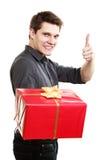 διακοπές Άτομο που δίνει το κόκκινο κιβώτιο δώρων που παρουσιάζει αντίχειρα Στοκ Φωτογραφίες