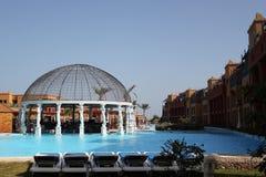 διακοπές στην Αίγυπτο με μια πισίνα ξενοδοχείων πολυτελείας με το μπλε νερό και έναν φραγμό με τα γλυπτά Στοκ Φωτογραφία